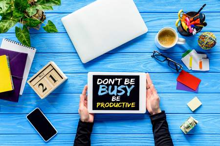 hands holding tablet on blue wooden table with money and stationery, Dont be busy be productive lettering Stock Photo