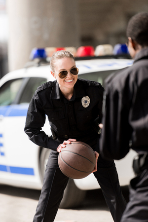young male and female police officers playing basketball