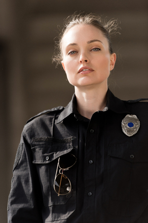 attractive female police officer in uniform looking at camera Stock Photo