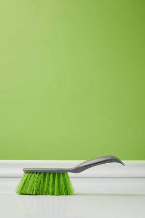 green brush for spring cleaning on floor Stock Photo