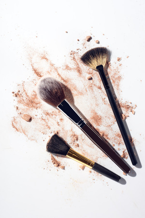 Broken face powder pieces and make up brushes on white background