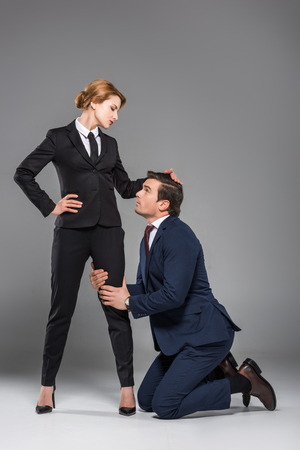 female boss dominating over scared businessman, isolated on grey, feminism concept 免版税图像