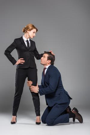 Jefa dominando al empresario asustado, aislado en gris, concepto de feminismo