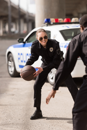 active young police officers playing basketball on street Stok Fotoğraf