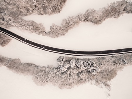 aerial view of asphalt road and snow-covered trees at winter, Germany 写真素材