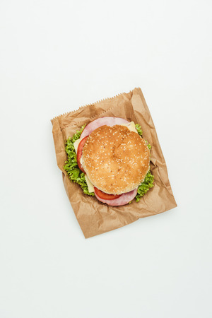 top view of burger with meat and vegetables on paper bag isolated on white