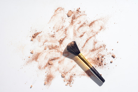 Scattered powder foundation with brush on white background Stock Photo