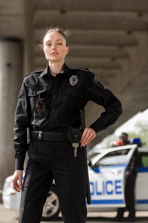 jolie femme policière en uniforme regardant la caméra avec un partenaire flou près de la voiture en arrière-plan