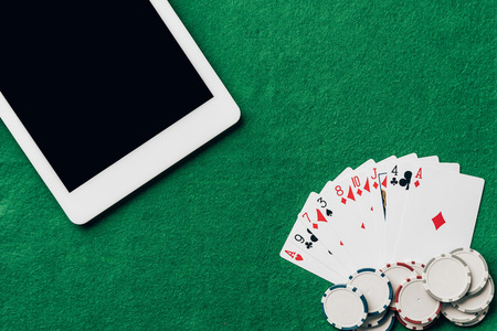 Online gambling with playing cards and chips by digital tablet Stock Photo
