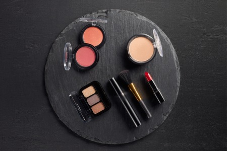 Make up set with eye shadows and blush on round slate background