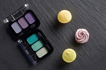 Eye shadows palettes with macarons and meringue on dark slate background
