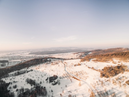 aerial view of beautiful snow-covered hills with bare trees at winter, Germany