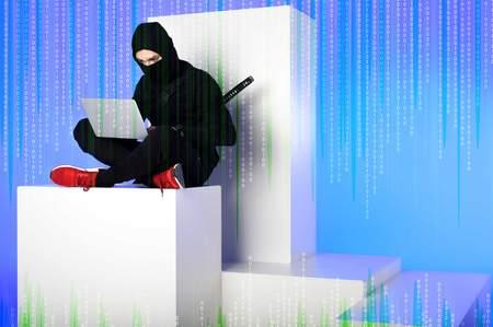 ninja in black clothing using laptop while sitting on white block with code on blue Zdjęcie Seryjne - 110798284