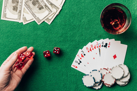 Female hand holding dice by casino table with money and cards
