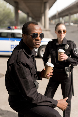 serious young police officers having coffee break
