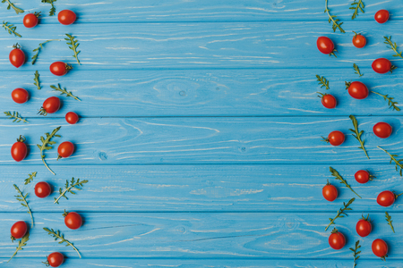 top view of cherry tomatoes with arugula on blue table Stock Photo