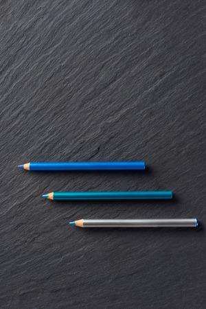 Make up pencils in blue tones on dark slate background
