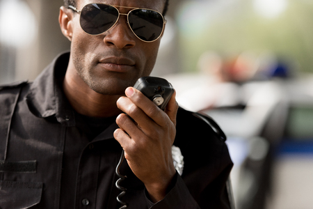 close-up portrait of african american police officer talking by walkie-talkie radio set