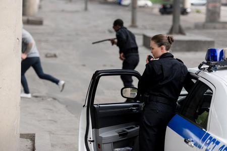 agents de police avec une voiture pourchassant un voleur dans la rue