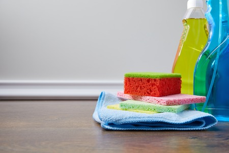 bottles with antiseptic liquids and rags for spring cleaning on floor Stock Photo