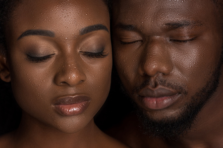 young african american couple with water drops on faces posing with closed eyes on black