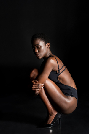 side view of beautiful african american girl in bodysuit crouching and looking at camera on black Stock Photo