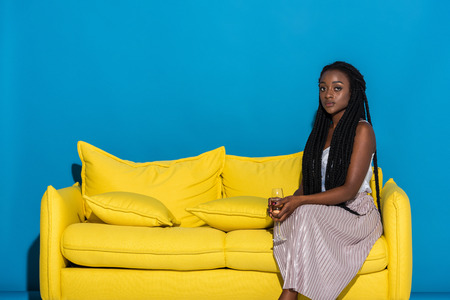 beautiful young african american woman holding glass of wine while sitting on sofa and looking at camera on blue