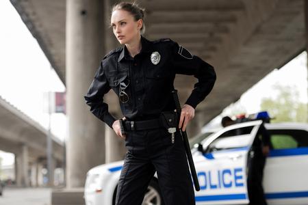 ufficiale di polizia femminile fiducioso che guarda lontano e tira fuori pistola e mazza Archivio Fotografico