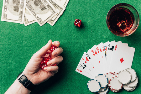 Woman holding dice by casino table with money and chips Stock Photo
