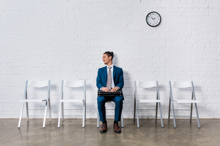 Curious man with briefcase waiting for interview while sitting on chair Stock Photo