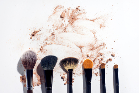 Set of brushes in a row on white background with scattered face powder