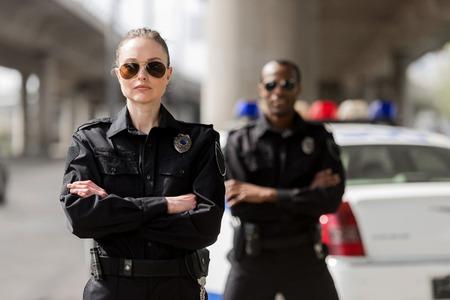 agents de police avec les bras croisés regardant la caméra devant la voiture Banque d'images