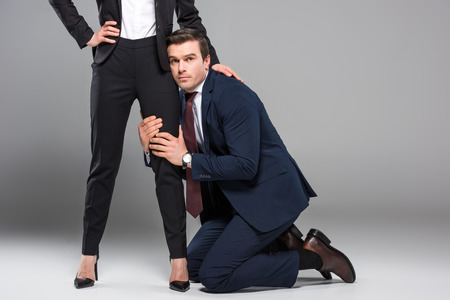 feminist businesswoman dominating over businessman, isolated on grey