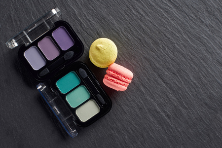 Eye shadows palettes with macarons on dark slate background
