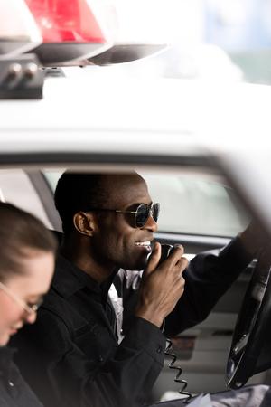 Nahaufnahme von jungen Polizisten, die im Polizeiauto sitzen Standard-Bild