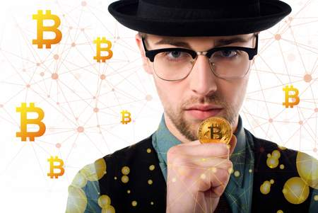 Portrait of man in eyeglasses and hat holding golden bitcoin on white Stock Photo