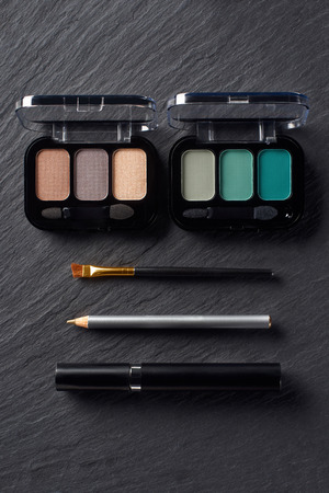 Palettes with eye shadows, pencil and mascara on dark slate background