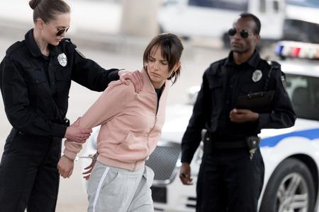 jeune policière tenant une criminelle menottée tandis que son partenaire se tient près Banque d'images