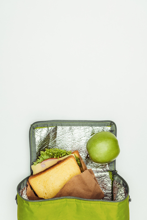 top view of sandwich and apple in lunch bag isolated on white