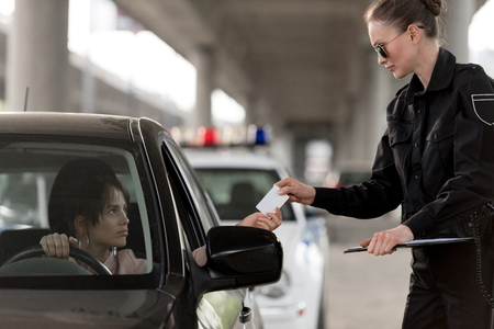 young woman in car giving driver license to policewoman in sunglasses Stock Photo