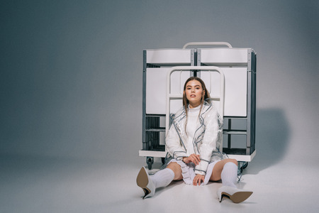 stylish woman in white clothing and raincoat with collapsible chairs behind looking at camera on grey background Stock fotó - 110816834