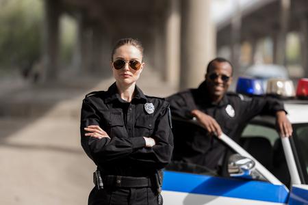 jeune policière sérieuse debout avec les bras croisés tandis que son partenaire debout près de la voiture et souriant flou sur fond