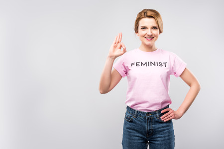 woman in pink feminist t-shirt showing ok sign, isolated on grey Фото со стока