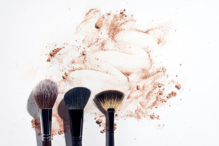 Three face brushes on white background with scattered face powder Stock Photo