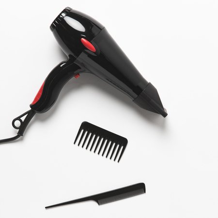 Top view of hair dryer and two combs, on white background