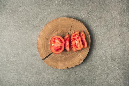 Top view of slices tomato on wooden stump on grey concrete tabletop 版權商用圖片
