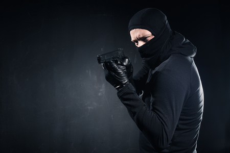 Male criminal in balaclava and gloves aiming with gun on black background Zdjęcie Seryjne