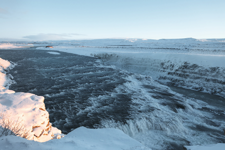 Beautiful Icelandic landscape with cold river, waterfall and snow-covered river banks 写真素材