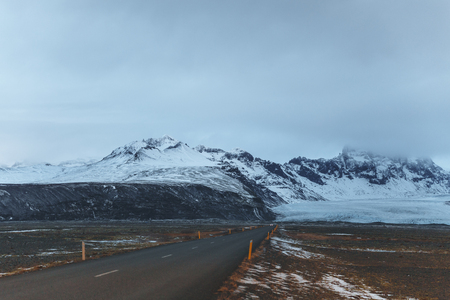 Empty asphalt road and beautiful snow-covered mountains in Iceland 写真素材
