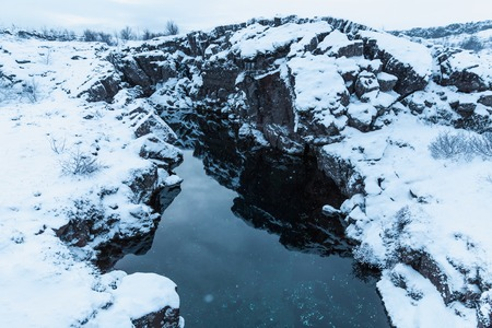 beautiful natural view of snow-covered rocks and cold water in thingvellir national park, iceland